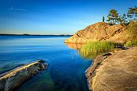 Klippa och man vid blå lugn fjärd vid Gålö i Stockholms skärgård