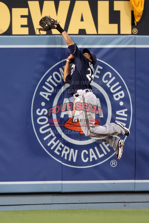 Carlos Gomez #27 of the Milwaukee Brewers makes a leaping catch at the wall during game against the Los Angeles Dodgers at Dodger Stadium in Los Angeles,California on May 16, 2011. Photo by Larry Goren/Four Seam Images