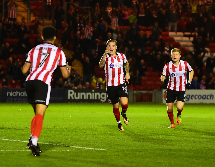 Lincoln City's Jordan Maguire-Drew, centre, celebrates scoring the opening goal with team-mates Josh Ginnelly, left, and Elliott Whitehouse<br /> <br /> Photographer Andrew Vaughan/CameraSport<br /> <br /> EFL Checkatrade Trophy - Northern Section Group G - Lincoln City v Everton U21s - Tuesday 24th October 2017 - Sincil Bank - Lincoln<br />  <br /> World Copyright &copy; 2018 CameraSport. All rights reserved. 43 Linden Ave. Countesthorpe. Leicester. England. LE8 5PG - Tel: +44 (0) 116 277 4147 - admin@camerasport.com - www.camerasport.com