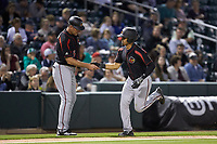 LaMonte Wade Jr. (4) of the Rochester Red Wings shakes hands with third base coach Joel Skinner (35) after hitting a home run against the Charlotte Knights at BB&T BallPark on May 14, 2019 in Charlotte, North Carolina. The Knights defeated the Red Wings 13-7. (Brian Westerholt/Four Seam Images)