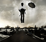 Conceptual image of a male figure hovering with angel wings and an umbrella