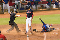 Home plate umpire Glen Meyerhofer calls AZL Indians 1 right fielder Johnathan Rodriguez (30) safe after he slid across home plate ahead of the tag from catcher David Garcia (9) during an Arizona League playoff game against the AZL Rangers at Goodyear Ballpark on August 28, 2018 in Goodyear, Arizona. The AZL Rangers defeated the AZL Indians 1 7-4. (Zachary Lucy/Four Seam Images)