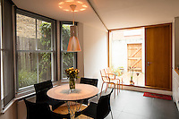 The Victorian home has been given a modernist aesthetic. The dining area has a retro feel and the new large picture window allows plenty of light into the room.