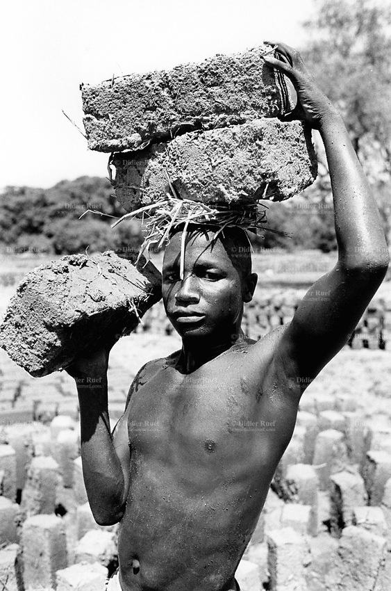 Guinea. High Guinea's state. Sembakounya (25 km from Dabola). Camp for Sierra Leoneans refugees. Young man with two bricks on his head and another one in his hand. Men are making bricks to build their house. One man can make in a day 100 to 120 bricks out of clay ground. Bricks have to dry one week under the sun before any use. A small family house  (2 rooms ) needs around 800 bricks.  © 2001 Didier Ruef