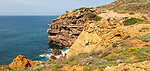 Coastal orange coloured crumbling  cliffs rise from Atlantic Ocean at Cabo de São Vicente, Cape St Vincent, Algarve, Portugal, southern Europe