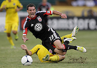 WASHINGTON, DC - AUGUST 4, 2012:  Chris Pontius (13) of DC United is tripped by Chris Birchall (8) of the Columbus Crew during an MLS match at RFK Stadium in Washington DC on August 4. United won 1-0.
