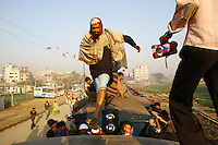 A passenger leaps from roof to roof across the gap between two train carriages. In Bangladesh many people ride on the roofs of trains as frequently that is the only space available. For others, the fares are too high and can be avoided or reduced by travelling on the roof. However, the riding on roofs and other parts of train exteriors leads to regular accidents, many of them fatal..
