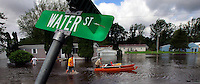 Cruel irony came in the form of a street sign as Tony Malone pushes a catamaran to help neighbors Calvin and Mike Jennings salvage items from their flooded home on Water Street in Cambridge.  Water from the swollen South Skunk River began rising into homes at 3 a.m.