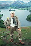 Portrait of the writer and artist Alfred Wainwright in the Lake District, Cumbria, England. Circa 1970. The lake is Grasmere. Wainwright stands on the path leading up to Loughrigg.