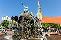Berlin, Germany. The Neptune Fountain was built in 1891. St. Mary's Church or Marienkirche on Alexanderplatz in the background.