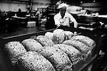 Baker readys freshly baked loaves for delivery