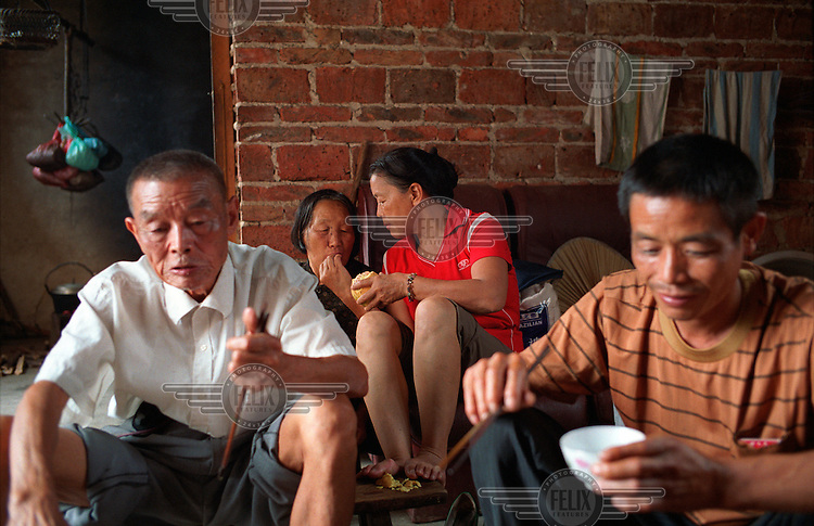 Family reunion at a village home near Quanzhou. The woman in centre wearing red works in the city while her parents and younger brother still live in the village.