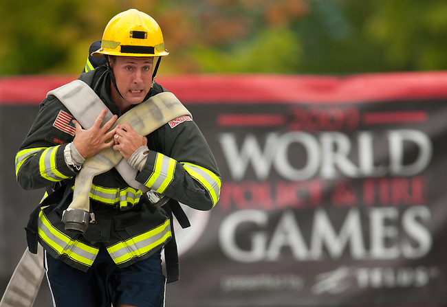 Vancouver, Canada, Aug 6th 2009.  World Police and Fire Games, Ultimate Firefighter Competition. Competitor Adam Griffin from the Seattle-Tacoma Airport Fire Department, USA, pulls hard during the Hose task portion of the competition. In this stage, competitors must drag two 150-foot long 2 ½-inch fire hoses their full length plus 30 feet, and then move to another station and roll up two 50-foot sections of hose and carry them back to the finish line.  Adam finished third in the senior A (ages 30-34) division with a combined time of 4:52.61 in the four stages.  Photo by Gus Curtis