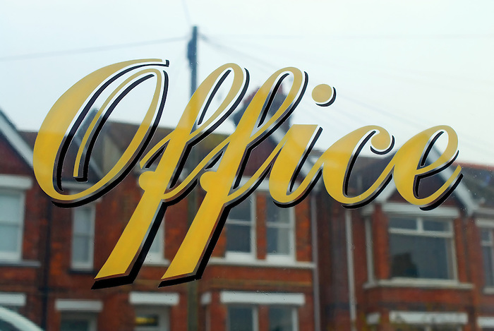 A sign reading 'Office' on a residential building window, with terraced houses reflected.