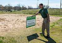 Jimmy Hutchison with Bentonville Parks and Recreation places a sign Wednesday, March 25, 2020, at the sand volleyball courts at Memorial Park in Bentonville. Bentonville Parks and Recreation staff removed nets from the sand volleyball courts Tuesday and from the adjacent tennis courts Wednesday. All Bentonville city parks have been closed, except for the trails, to combat the spread of the covid-19 pandemic.    <br /> Go to nwaonline.com/photos to see more photos.<br /> (NWA Democrat-Gazette/Ben Goff)