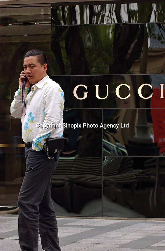 People pass a Gucci store in down-town Shanghai, China. Gucci and many other top-end designers are expanding into China despite the proliferation of fakes easily available..23 Apr 2005