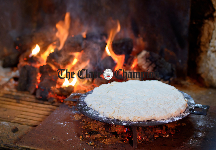 Griddle bread baking by the coals of the open hearth during a cultural visit to The Rambling House in Kilmurry Mc Mahon by pupils of Labasheeda National School. Photograph by John Kelly.