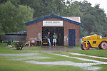 © Joel Goodman - 07973 332324 . 28 July 2013 . Rochdale Cricket Club , Bridgefold Road , OL11 5BX , UK . As rain pours down , men stand looking grumpy in the doorway of the building with the scores on it and the match between Rochdale and Clifton CC is abandoned . Photo credit : Joel Goodman