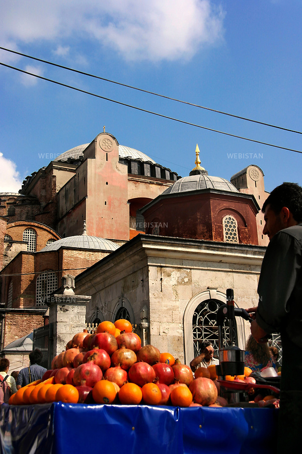 Turkey, Istanbul, Hagia Sophia, October 5, 2012A local vendor sells fresh oranges and pomegranates at a fruit stand in front of the Hagia Sophia.Hagia Sophia (meaning Holy Wisdom) is one of the most renowned monuments in Istanbul and the most important Byzantine structure. Construction of the original Hagia Sophia began in the year 360 by the first Christian Emperor, Constantine the Great. The church was reconstructed from 408-450 and then demolished during the Nika riots of 532. The current structure was rebuilt from 532-537 under the supervision of Emperor Justinian I. The basilica served as a Greek Orthodox Cathedral and then became a Roman Catholic Church after the 1204 attack by the Crusaders. When Fatih Sultan Mehmed II conquered Constantinople in 1453, he converted Hagia Sophia into a mosque. Hagia Sophia served as the principal mosque of Istanbul for almost 500 years. In 1934, under Turkish president Mustafa Kemal Ataturk, Hagia Sofia was secularized and turned into the Ayasofya Museum.   <br /> Turquie, Istanbul, Basilique Sainte Sophie, 5 octobre 2012Un vendeur local vend ds oranges et des grenades en face de Sainte-Sophie.Hagia Sophia ( signifiant Sainte Sagesse ) est l'un des monuments les plus celebres d'Istanbul et sa structure byzantine en est la plus importante. La construction de la basilique Sainte-Sophie a commence en l'an 360 sous le premier empereur chretien, Constantin le Grand. L'eglise a ete reconstruite de 408 a 450, puis demolie durant les emeutes de Nika 532. La structure actuelle a ete reconstruite en 532-537 sous la supervision de l'empereur Justinien I. La basilique a servi de cathedrale orthodoxe grecque et est ensuite devenue une eglise catholique romaine apres l'attaque des Croises en 1204. Lorsque le Sultan Fatih Mehmed II a conquis Constantinople en 1453, il a converti Sainte-Sophie en mosquee. Elle fut la principale mosquee d'Istanbul pour pres de 500 ans. En 1934, sous la presidence turque de Mustafa Kemal Ataturk, Hagi
