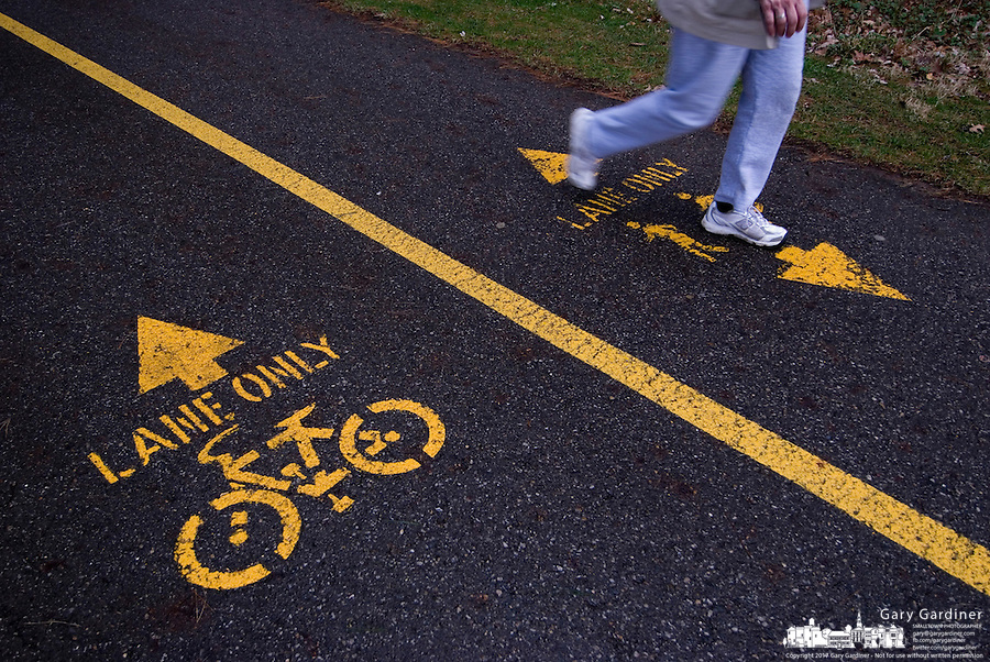 A woman walks in the jogging side of an exercise path through a park. The other side of the path is reserved for bicycles.<br />