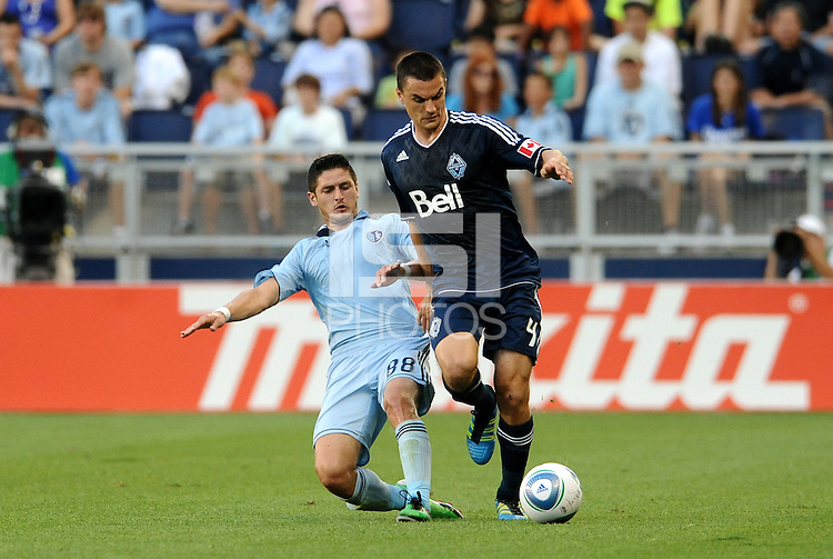 Alain Rochat (4) Vancouver Whitecaps defender holds off the challenge of Sporting KC midfielder Milos Stojcev... Sporting KC defeated Vancouver Whitecaps 2-1 at LIVESTRONG Sporting Park, Kansas City, Kansas.