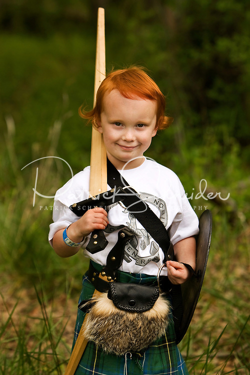 A young red headed boy stands at the Loch Norman games in Huntersville, NC.