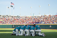 The Coastal Carolina Chanticleers kneel together prior to a College World Series Finals game between the Coastal Carolina Chanticleers and Arizona Wildcats at TD Ameritrade Park on June 28, 2016 in Omaha, Nebraska. (Brace Hemmelgarn/Four Seam Images)