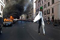 Un manifestante sfila alla manifestazione mentre una auto viene data alle fiamme.A protestor march by a parked car on fire