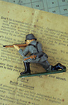 Lead model of German or Russian soldier kneeling and aiming rifle lying on booklet of British advice to captured airmen