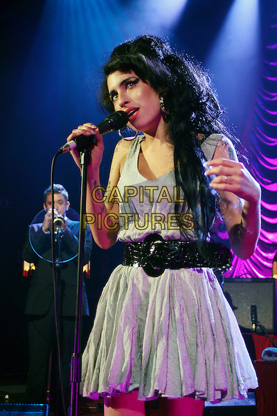 AMY WINEHOUSE.Live in concert at the Shepherd's Bush Empire, London, England..May 28th, 2007.gig performance music half length grey gray dress back belt singing tattoos .CAP/MAR.© Martin Harris/Capital Pictures.