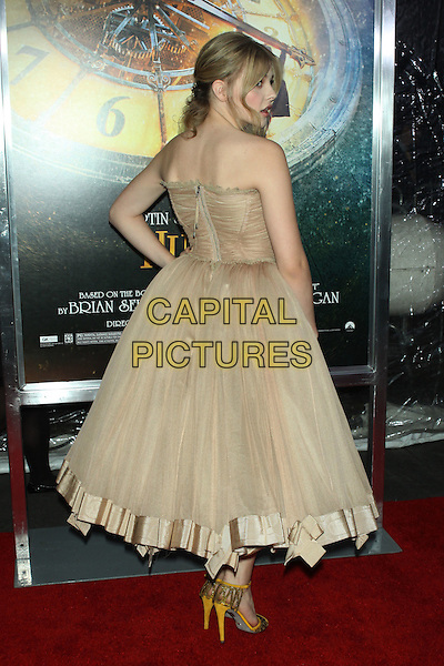 "Chloe Grace Moretz  .The World Premiere of ""Hugo"" held at the Ziegfeld Theatre, New York, NY, USA..November 21st, 2011.full length beige strapless dress hand on hip sheer silk satin profile back behind rear looking over shoulder zip zipper .CAP/LNC/TOM.©LNC/Capital Pictures."