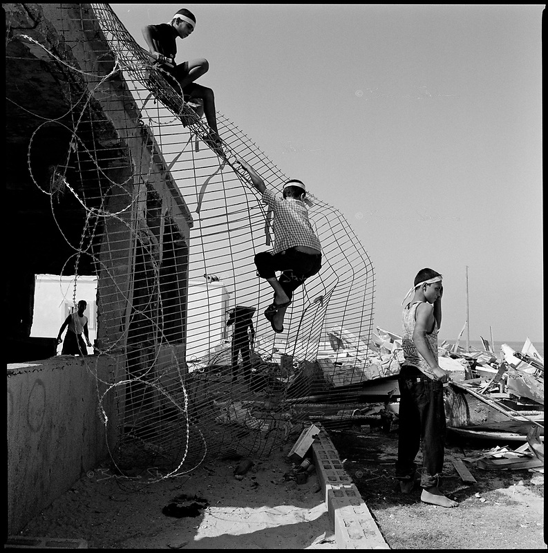 former Shirat Ayam settlement, Sept 12 2005..Palestinian teenagers on the roof of the last house abandonned by the Jewish settlers, barely 2 weeks previously. Hours after the Israeli left the area, thousands Khan Younes inhabitants rushed to the beach, formerly Shirat Hayam Jewish settlement, less than 3 kilometers from their homes.