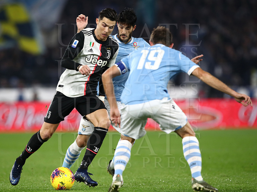 Football, Serie A: S.S. Lazio - Juventus Olympic stadium, Rome, December 7, 2019. <br /> Juventus' Cristiano Ronaldo (l) in action with Lazio's captain Senad Lulic (r) and Luis Alberto (c) during the Italian Serie A football match between S.S. Lazio and Juventus at Rome's Olympic stadium, Rome on December 7, 2019.<br /> UPDATE IMAGES PRESS/Isabella Bonotto