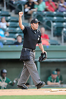 Umpire Grant Conrad works home plate in a game between the Greensboro Grasshoppers and the Greenville Drive on Wednesday, August 26, 2015, at Fluor Field at the West End in Greenville, South Carolina. Greenville won, 7-0. (Tom Priddy/Four Seam Images)