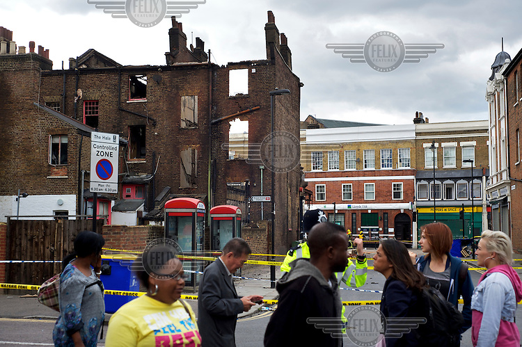 Local residents talk to a policeman near a corndoned off area and damaged buildings where rioting took place two nights earlier in Tottenham, London borough of Haringey. London saw the beginnings of riots on Saturday evening, after a peaceful protest in response to the shooting by police of Mark Duggan during an attempted arrest, escalated into violence. By the third night of violence, rioting had spread to many areas of the capital and to other cities around the country.