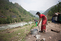 Tej Kumari Shrestha, 65, collects water from a source at Shila Porbot, outskirts of Kathmandu, Nepal. Tej Kumari Shrestha lost her home in Nepal earthquake and lives in a temporary house in the bank of a river. May 8, 2015