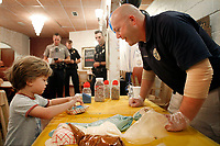 NWA Democrat-Gazette/DAVID GOTTSCHALK Finn Ramser, 4, picks up his glazed donut Wednesday, October 3, 2018, after adding sprinkles with the help of Corporal Dallas Brashears during the Fayetteville Police Department Coffee with a Cop event at Rick's Bakery in Fayetteville. Members of the department, including Chief of Police Greg Tabor, were on hand to visit with members of the community to answer questions, listen to concerns and get to know the officers. Free coffee and a donuts sprinkle bar were available.