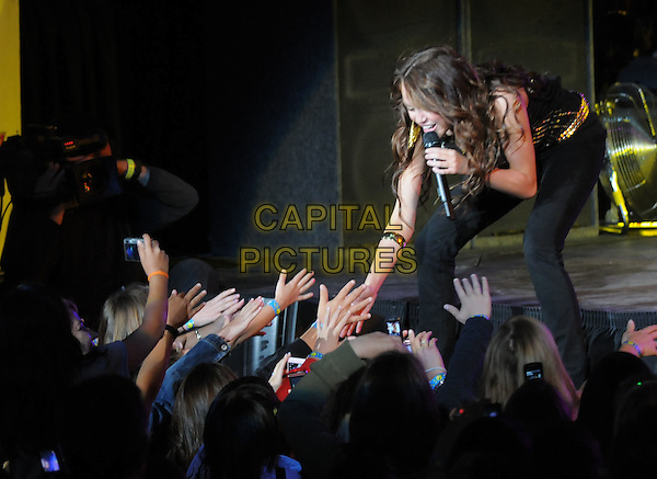 MILEY CYRUS .Live at The KIIS Fm Wango Tango 2008 held at The Verizon Wireless Ampitheatre in Irvine, California, USA, May 10th 2008..music concert gig on stage half length holding touching fans hands .CAP/EAS.©Eastman/Capital Pictures