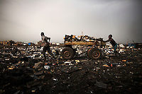 Children push a cart loaded with scrap, including computers keyboards and other e-waste, at Agbogbloshie dump, which has become a dumping ground for computers and electronic waste from all over the developed world. Hundreds of tons of e-waste end up here every month. It is broken apart, and those components that can be sold on, are salvaged.