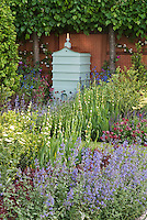Beehive in beautiful spring garden with bee friendly attracting plants, including Nepeta