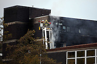 Pictured: Fire fighters on an aerial unit at the scene of a large fire at the Gower College Swansea in the Tycoch area of Swansea, Wales, UK. Friday 28 October 2016<br />Re: About 100 firefighters have been tackling a large fire at Gower College Swansea.<br />Mid and West Wales Fire Service was called to Gower College on Tycoch Road, Sketty, just before 4:30am on Friday.<br />It said the fire covered the second and third floors of a four-storey building but it is now under control.<br />There were about 20 fire appliances at the scene, the incident is ongoing and Tycoch Road is shut.