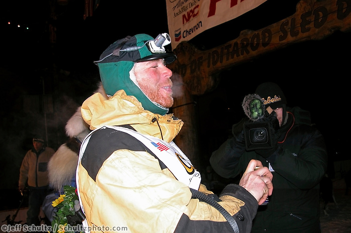 Zack Steer celebrates his arrival in Nome in third place. Photo by Jon Little.