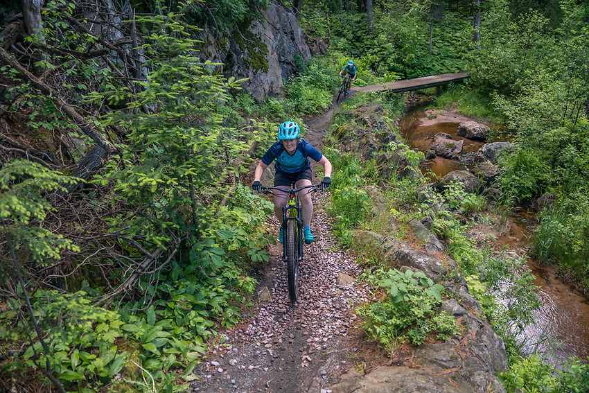Mountain biking along the Dead River on the Noquemanon Trails Network North Trails in Marquette, Michigan.