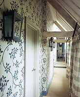 The hallway leading to the kitchen has been lined with grey and white floral wallpaper with woodwork picked out in a complementary tone