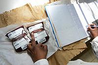 RWANDA, Butare, health center Gikonko, blood preserves delivered by zipline drone / RUANDA, Butare, Institut Saint Boniface, Krankenstation Gikonko, Labor, Mitarbeiter Job packt Blutkonserven aus, die gerade per zipline Drohne gekommen sind
