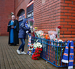 A young Rangers supporter places flowers at the memorial statue at Ibrox Stadium to remember the 66 supporters who never made it back home on 2nd January 1971