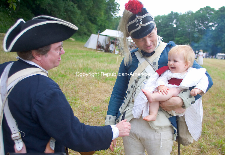 "SOUTHBURY, CT - 17 JUNE 2006 - 061706JW13.jpg -- Revolutionary war reenactors George Bock of Bedford Hills, NY and William Chamberlain of Holliston, Ma. joke about sending over to the enemy Chamberlain's ""24 pounder"" his son Frank Chamberlain age 11 months, before the major battle of the day during the Rochambeau weekend Saturday morning. This is the first reenactment event for the infant. Jonathan Wilcox Republican-American"