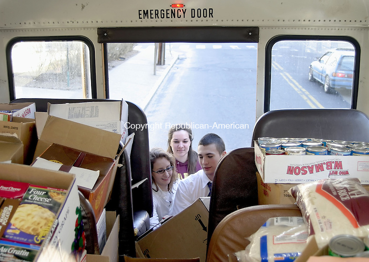 WATERBURY, CT -30 MARCH 2007 - -033007DA01-- Sacred Heart High School students From left, Alexandra Cote, Courtney Ambrose, and Stephen Corbo, help load a school bus with nonperishable foods after a food drive that was organized by the National Honor Society and will deliver over 5000 cans of food to St. Vincent DePaul shelter in Waterbury Friday afternoon. <br />  Darlene Douty/Republican-American
