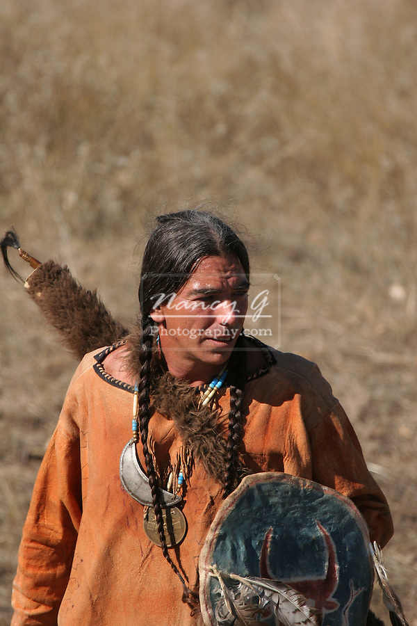 A Native American Indian man standing with a shield