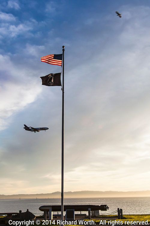 The US Flag, POW-MIA Flag, a bird and a plane - all flying at San Leandro Marina along San Fancisco Bay.